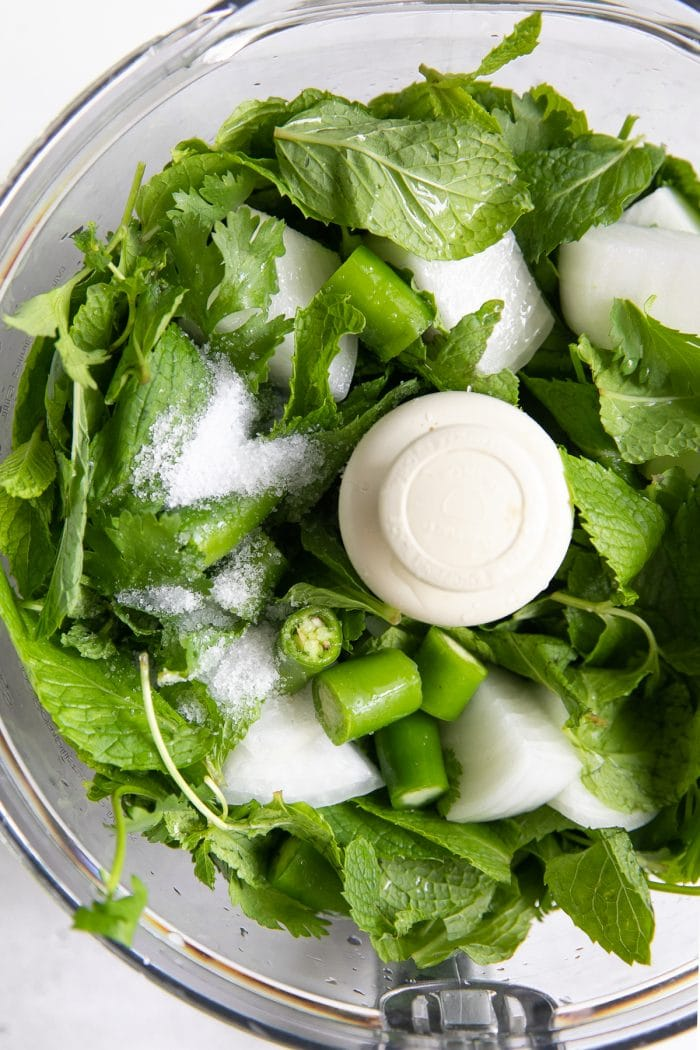 Food processor filled with fresh mint, cilantro, onion, green chili, and salt.