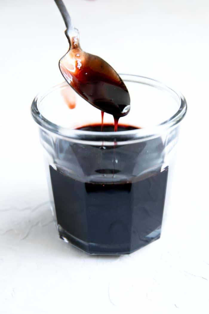 Glass jar filled with syrupy pomegranate molasses.l