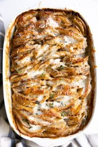 Golden cheesy potatoes au gratin in a white casserole dish.