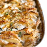 Baking dish filled with cheesy baked thinly sliced potatoes in a cream sauce.