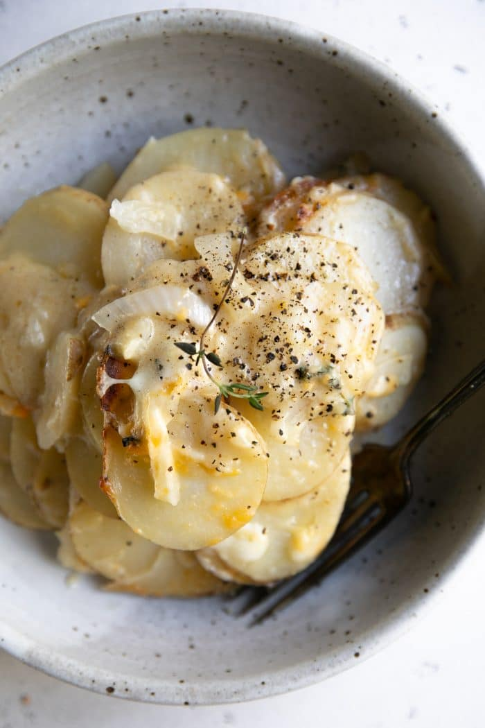 Bowl filled with thinly sliced potatoes au gratin.