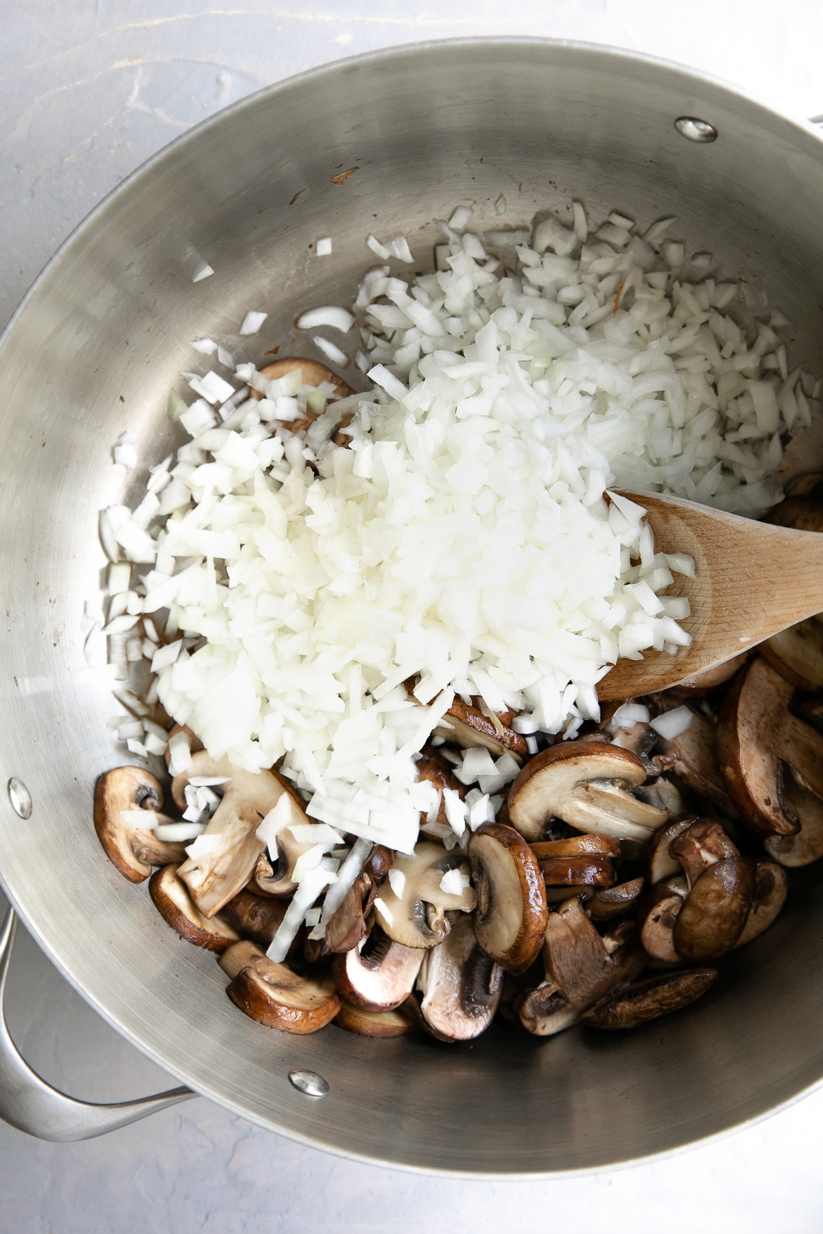 Mushrooms and diced onions in a large pot.