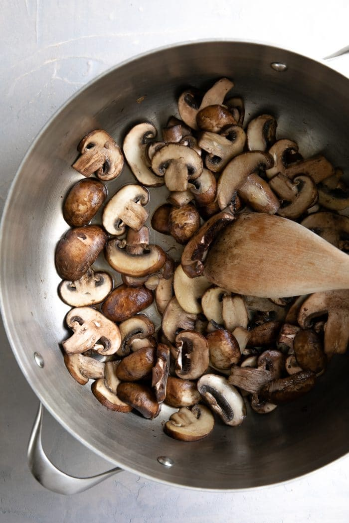 Mushrooms cooking in a large skillet.