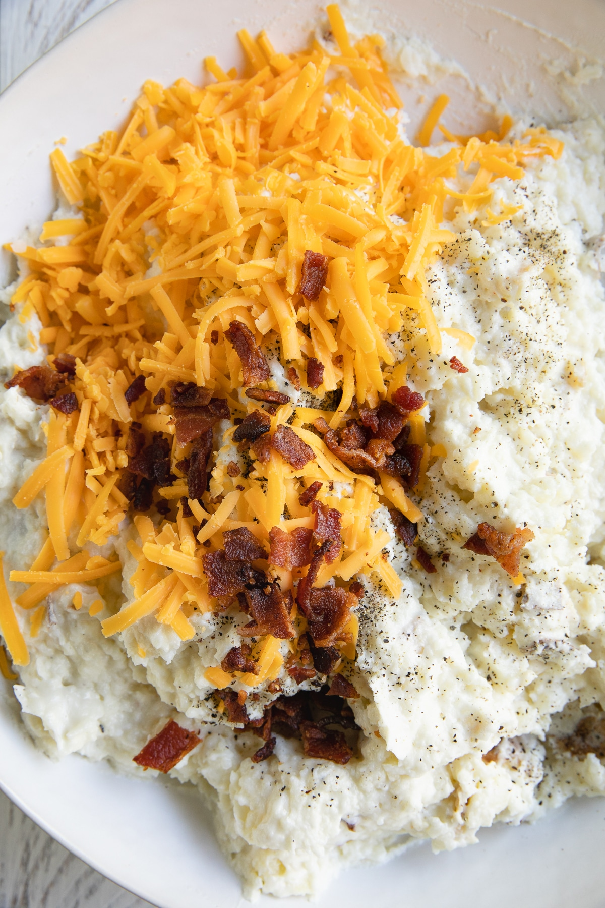 Large white mixing bowl filled with creamy mashed potatoes, shredded cheddar cheese, and bacon bits.