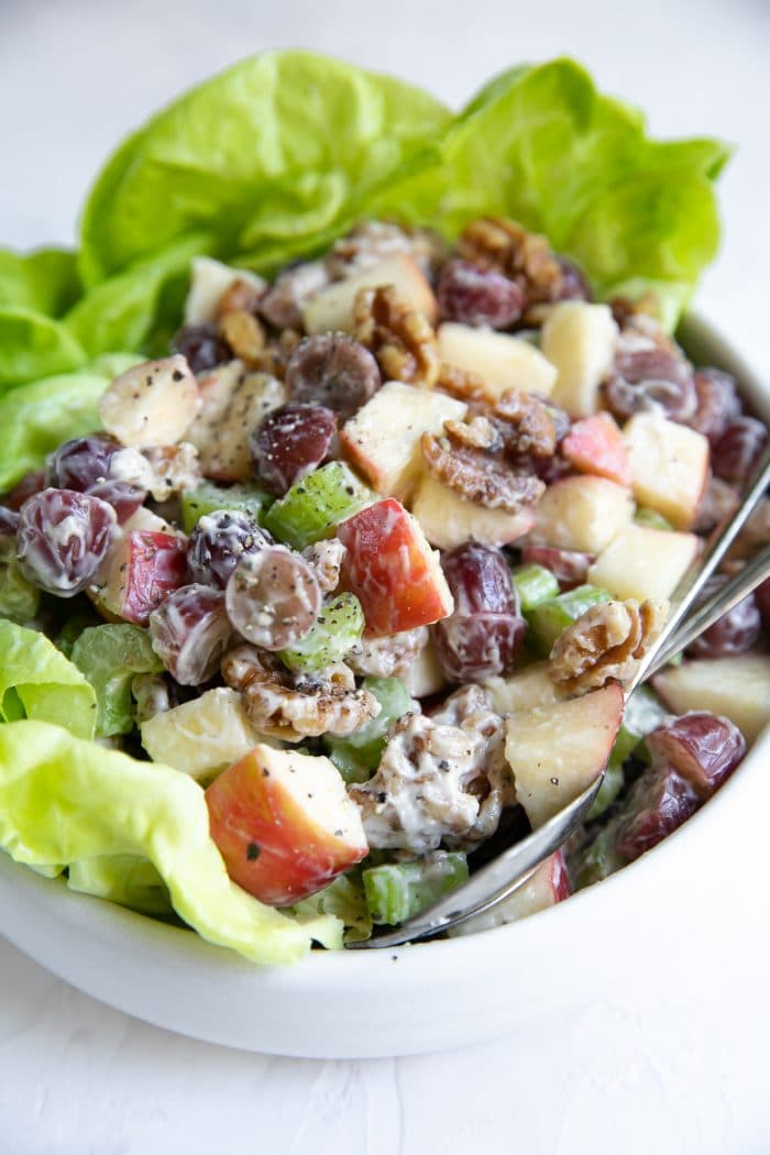 Waldorf salad made with apples, walnuts, grapes, and celery on a bed of lettuce in a white serving bowl.