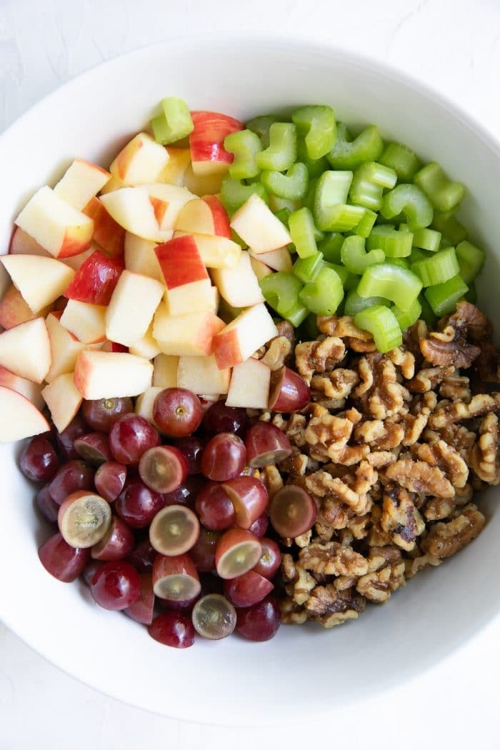 Large white salad bowl filled with chopped celery, diced apples, red grapes, and toasted walnuts.