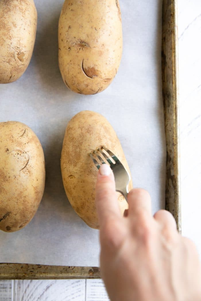 Russet potato being poked with a fork.