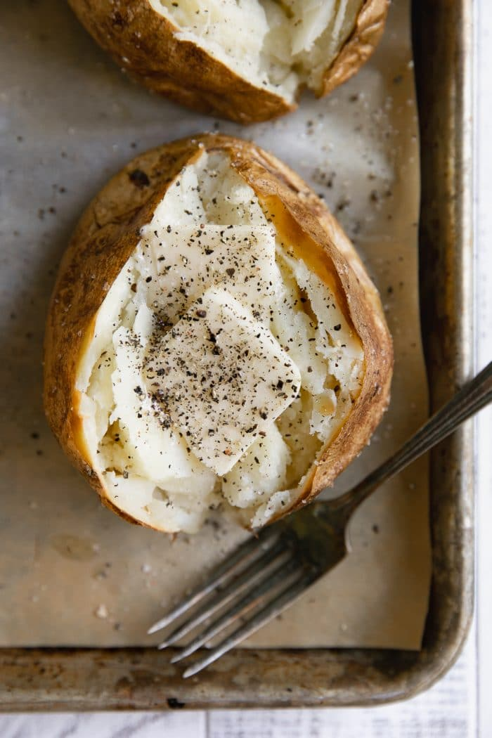 Overhead image of fully cooked baked potato topped with butter and seasoned with salt and pepper.