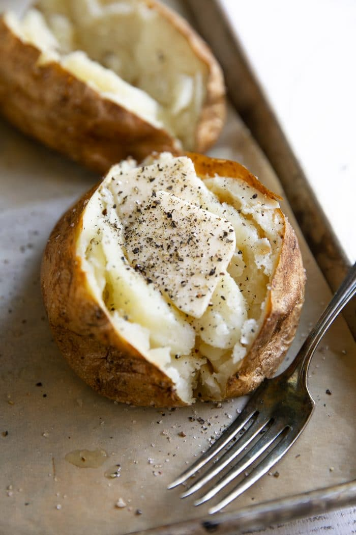 Fully cooked baked potatoes cut in half and seasoned with salt, pepper, and butter.