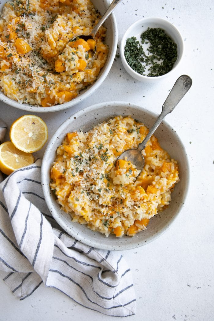 Two shallow ceramic bowls filled with creamy butternut squash risotto garnished with parmesan cheese and fresh sage.