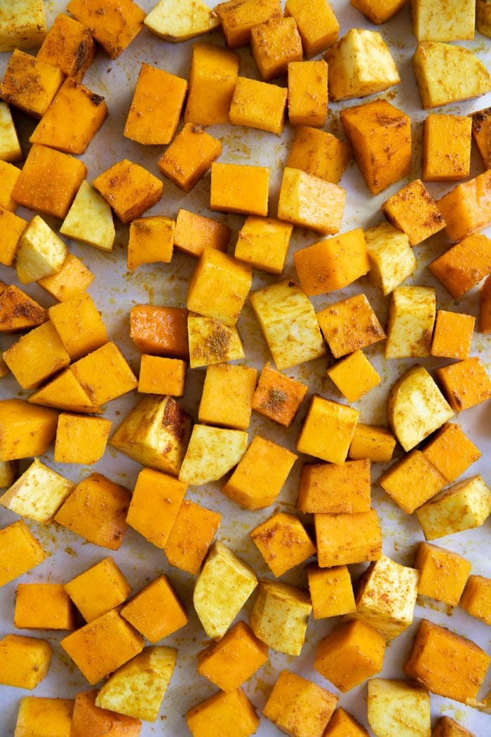 Cubes of raw butternut squash coated in spices and spread on a baking sheet.