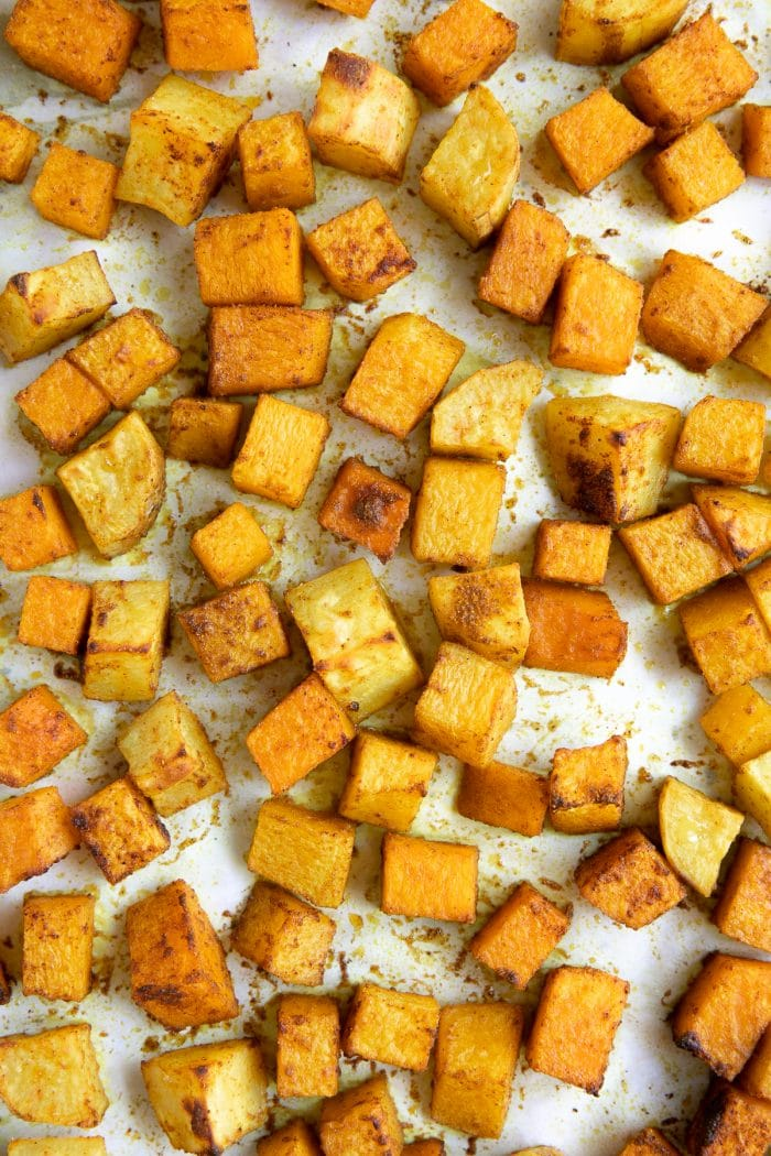 Baking sheet covered with cubes of roasted spice-covered butternut squash.