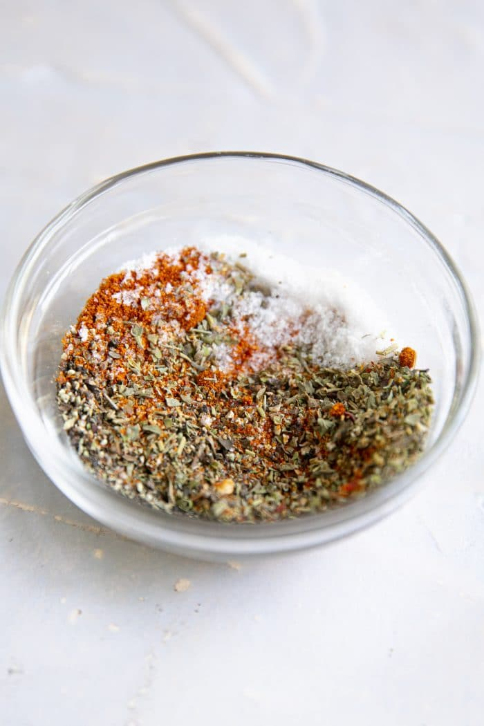 Small glass bowl filled with a mixture of dried Italian seasoning, paprika, salt, and pepper.