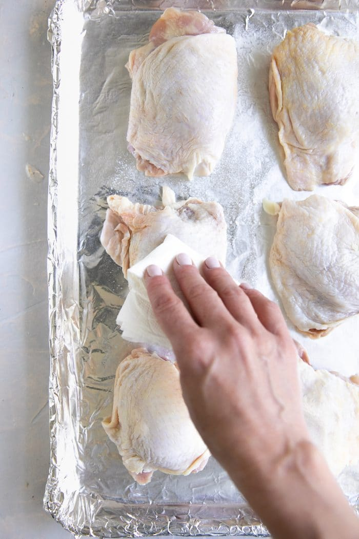 Patting bone-in skin-on chicken thighs with a paper towel.