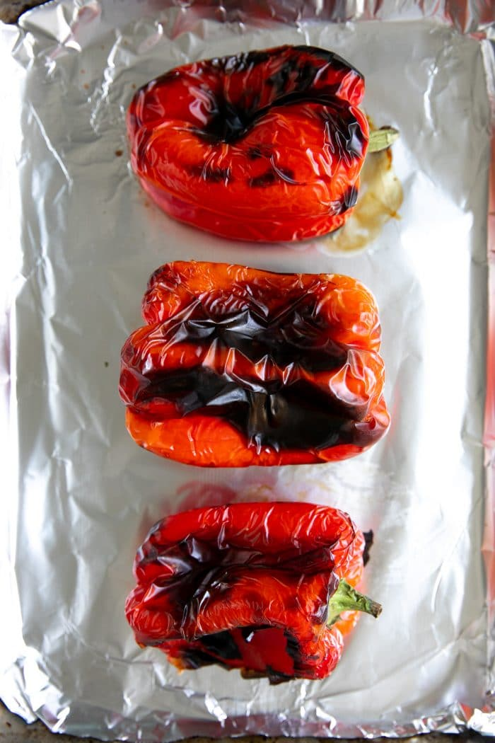 Three whole roasted red bell peppers with blackened skin on a large baking sheet.