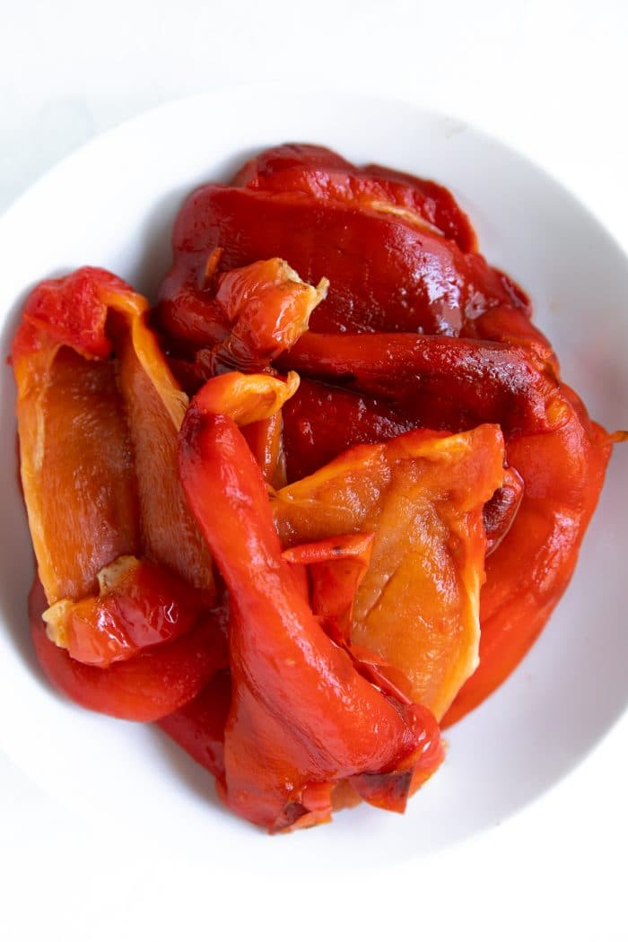 White bowl filled with roasted peeled red bell peppers.