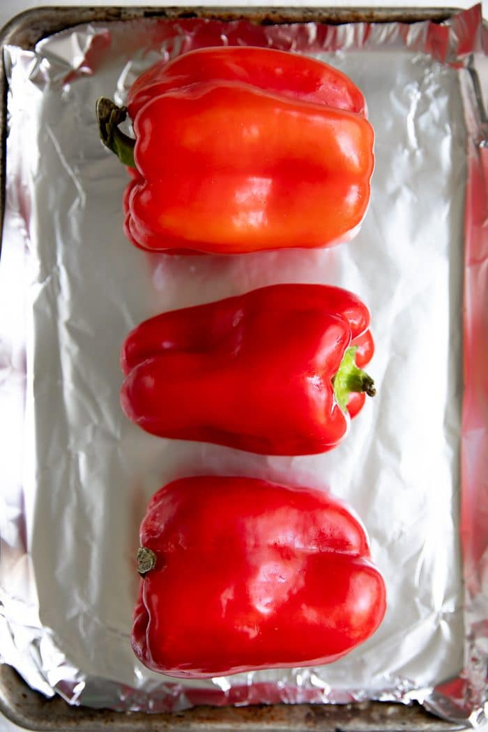 Three whole red bell peppers on a baking sheet lined with aluminum foil.