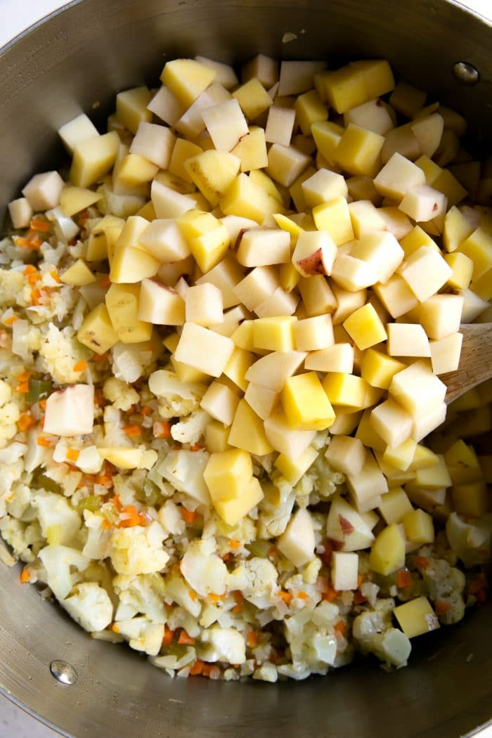 Finely minced onion, celery, and carrots, cooking in a large pot with finely chopped cauliflower and diced potatoes.