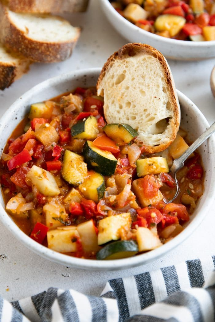 White shallow bowl filled with homemade Italian ratatouille and served with fresh toasted bread.