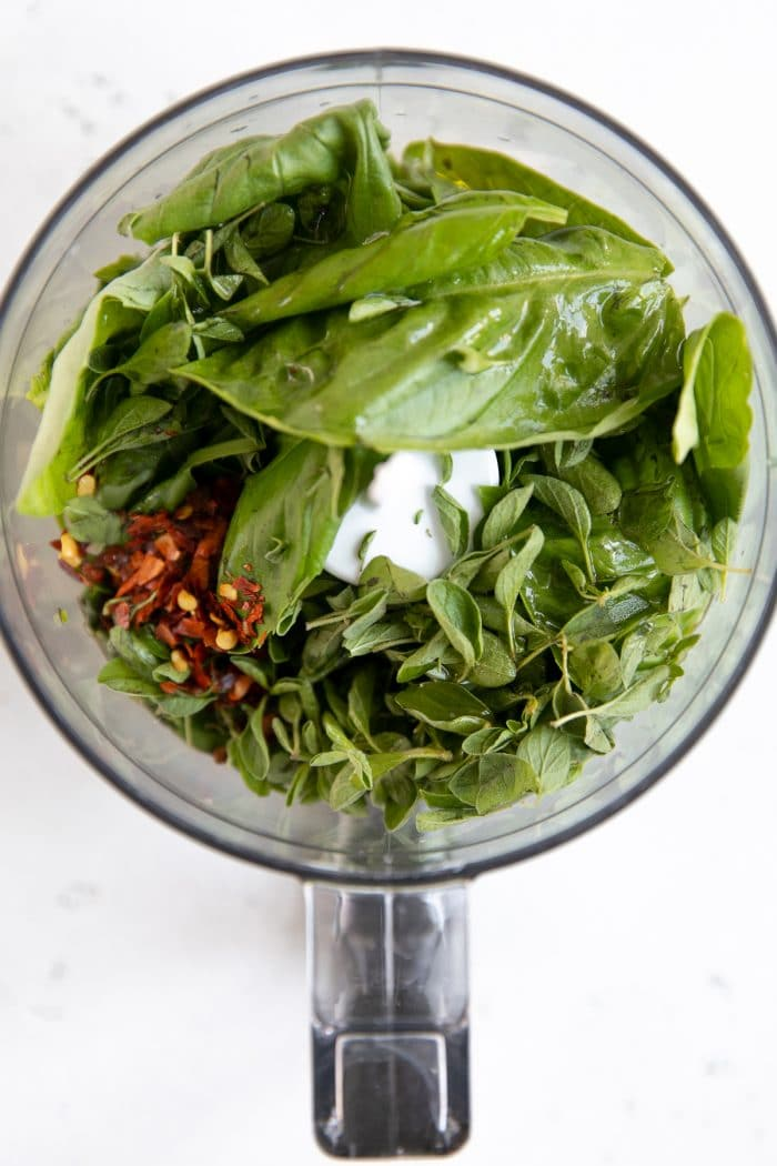Small food processor filled with fresh oregano, fresh basil, olive oil, garlic, and red chili flakes.