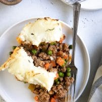 Big slice of homemade classic shepherd's pie on a white serving plate.