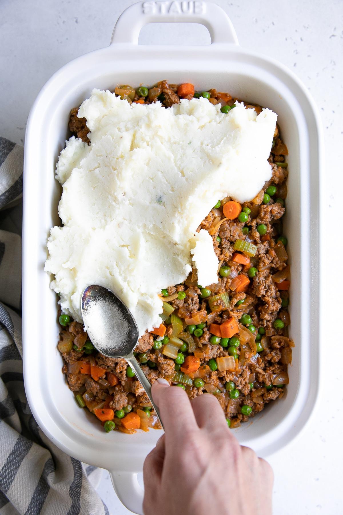 Assembling Shepherd's Pie in a large white casserole dish.