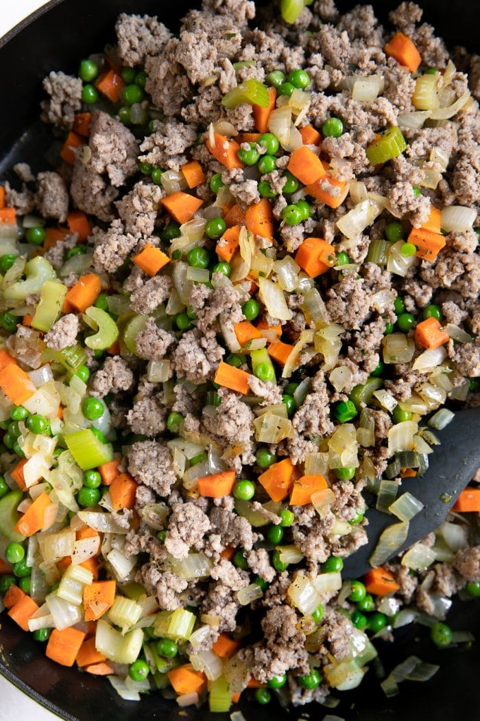 Onions, carrots, peas, celery, and ground beef and lamb cooking in a large cast iron skillet.