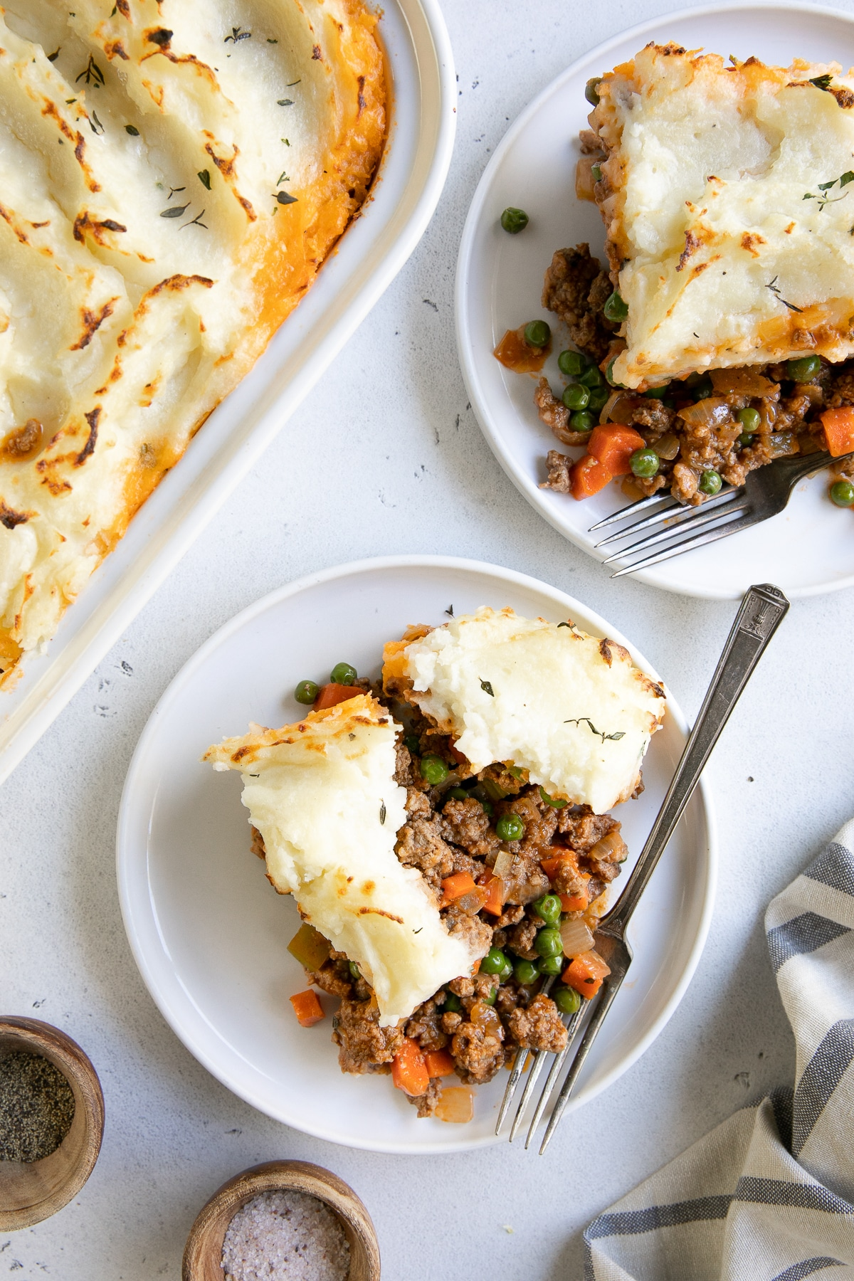 Two white serving plates with a big slice of homemade classic shepherd's pie.