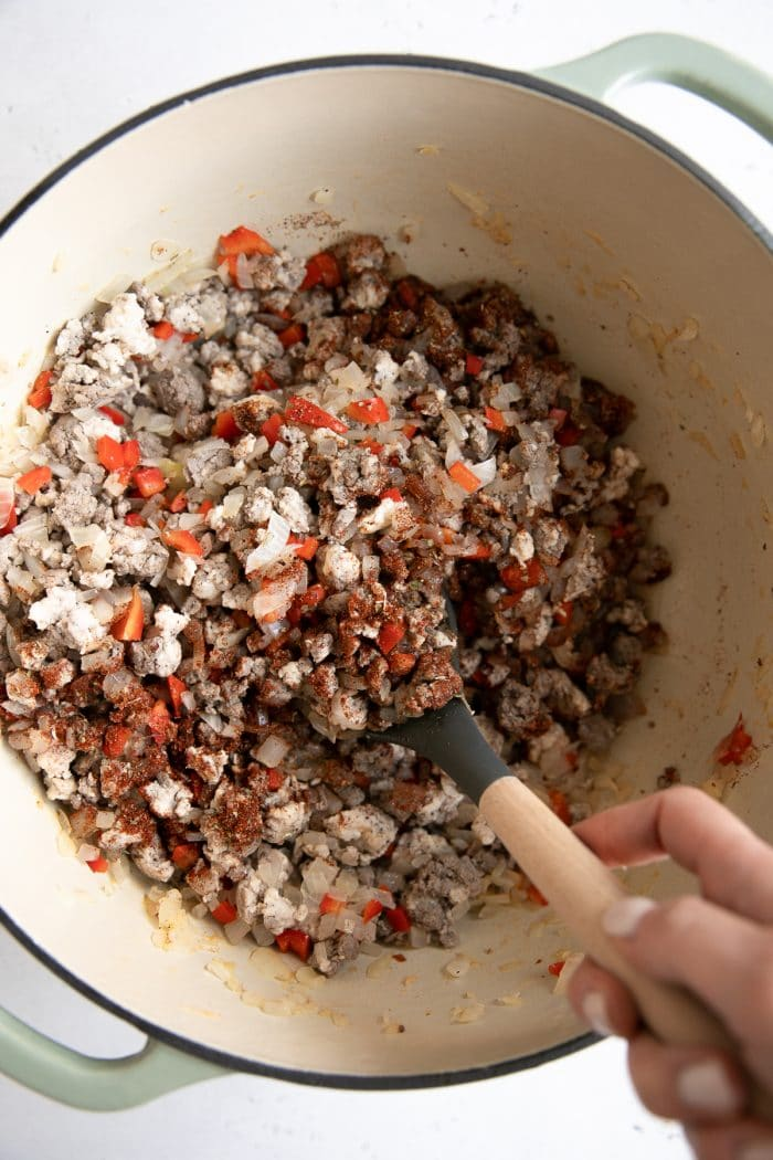 Ground turkey, ground beef, bell peppers, onion, and garlic, covered in taco seasoning and cooking in a large pot.
