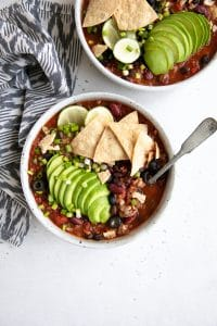 Overhead image of two white shallow bowls filled with homemade taco soup and topped with sliced avocado, tortilla chips, green onions, and lime wedges.