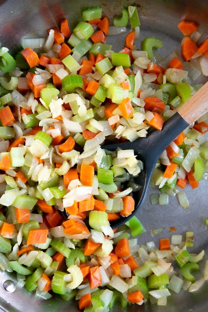 Large skillet filled with finely chopped carrots, celery, and onions.