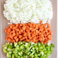 Cutting board with finely chopped onion, carrots, and celery.