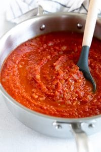 Ladle in a large shallow saucepan filled with Spicy Arrabbiata Sauce.