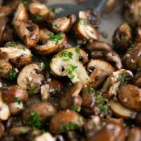 Mushrooms sauteeing in a large skillet with butter and garlic and sprinkled with fresh parsley.