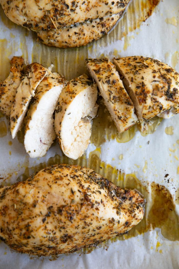 Three baked chicken breasts covered in homemade poultry seasoning.