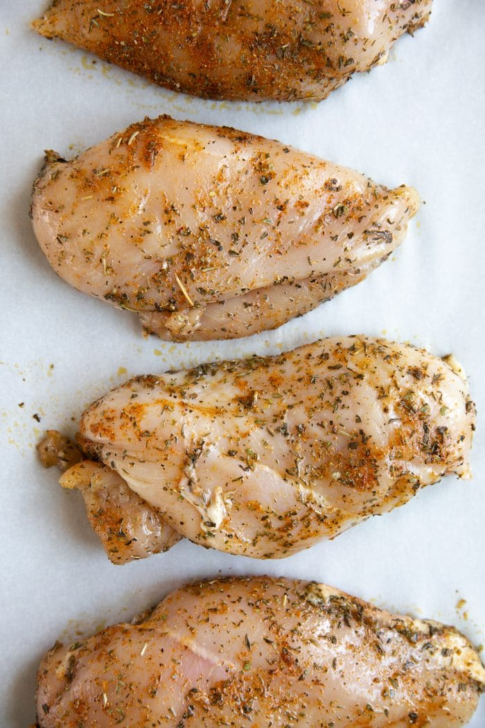Four raw chicken breasts covered in poultry seasoning.