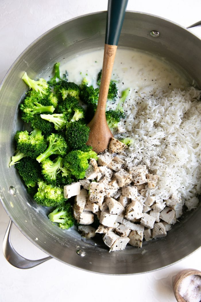 Large pot filled with homemade cream sauce, cooked rice, chicken, and blanched broccoli.