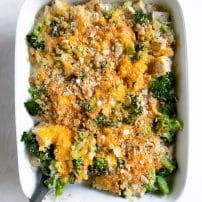 Overhead image of a large white casserole dish filled with creamy baked broccoli, chicken, and rice casserole topped with melted cheddar cheese.