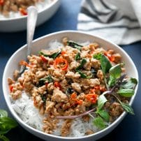 White shallow bowl filled with cooked white rice and topped with prepared thai basil chicken.