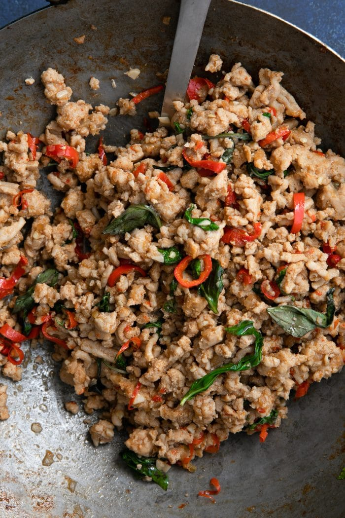 Large wok filled with cooked Thai Basil Chicken made with ground chicken cooked with thai basil, chilis, and different sauces.