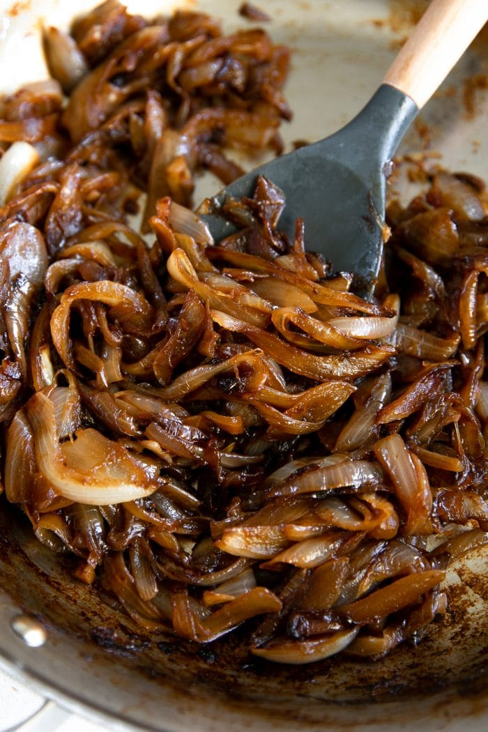Close-up image of caramelized onions in a large stainless steel skillet.