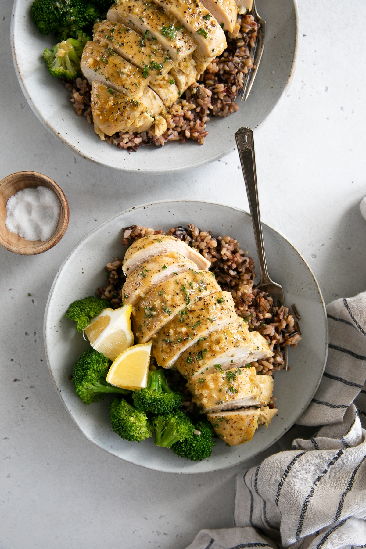 Two white plates with sliced honey mustard chicken breast over a bed of cooked rice and served with steamed broccoli and fresh lemon.
