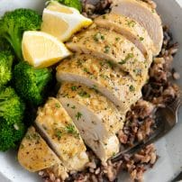 Sliced chicken breast over a bed of cooked rice and served with steamed broccoli and fresh lemon.