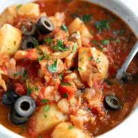 Bacalao made with salted cod, tomatoes, potatoes, shallots, and black olives.