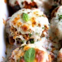 White baking dish filled with crispy eggplant layered with gooey melted cheese and tomato sauce.