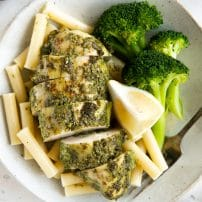 Plate with steamed broccoli, plain boiled pasta noodles, and pesto covered chicken breast.