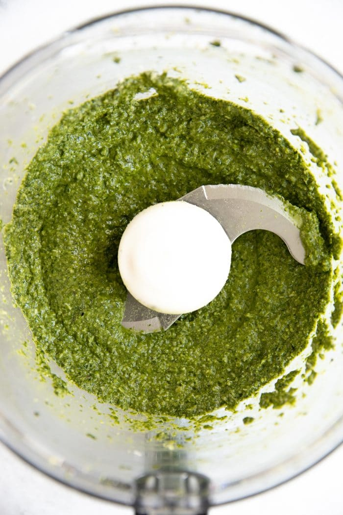 Processed basil, olive oil, pine nuts, parmesan cheese, and garlicin a large food processor.