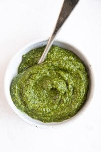 Small white bowl filled with homemade pesto recipe.