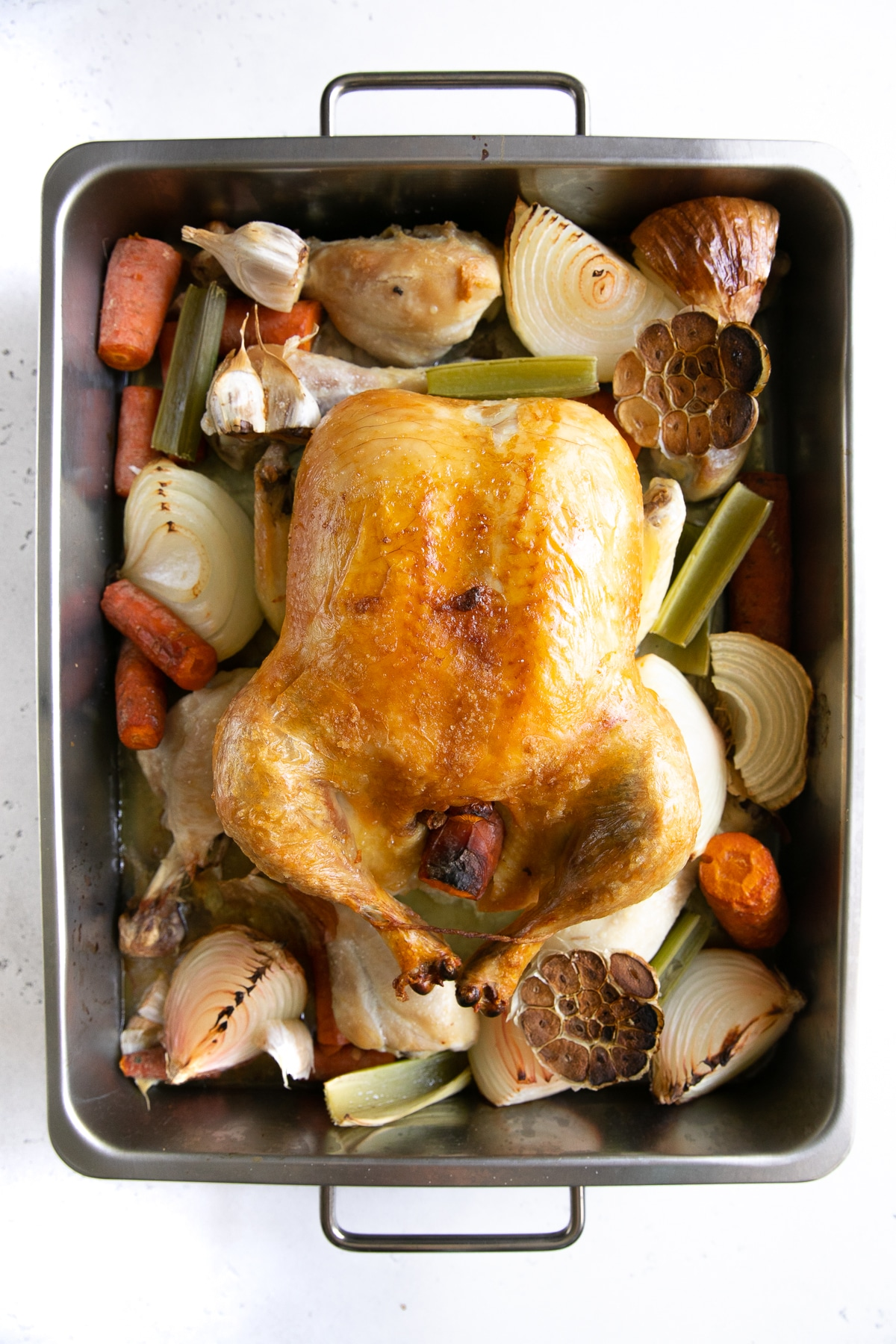 Whole browned chicken and vegetables in a large roasting pan.
