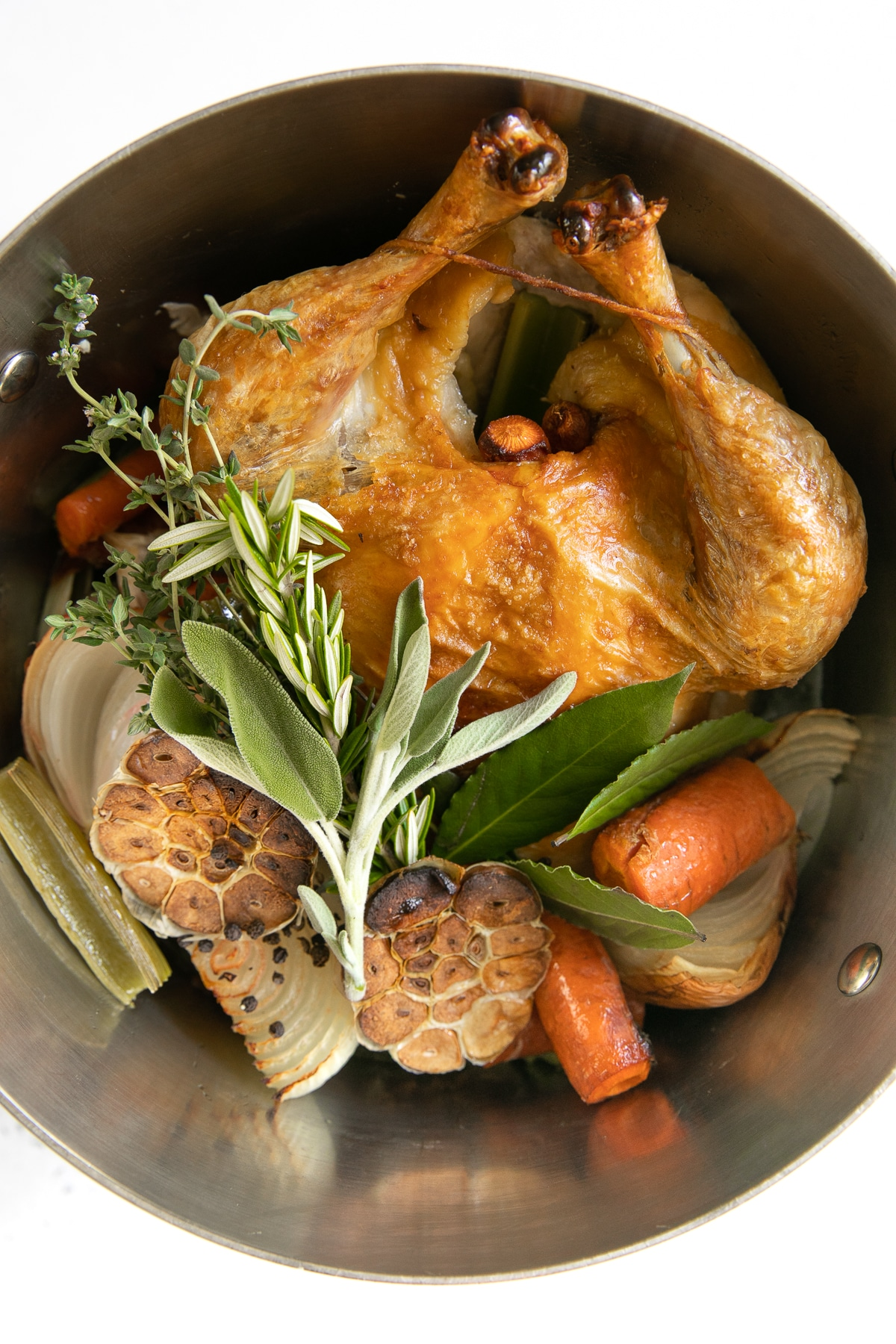 Large stock pot filled with one whole browned chicken, garlic, vegetables, and fresh herbs.